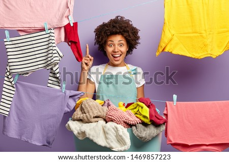 Housekeeping and washing concept. Happy dark skinned female housekeeper wears apron, hangs clean washed clothes on rope, raises index finger, has brilliant idea how to remove stain on shirt. #1469857223