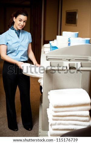 Housekeeping in charge pulling out the bath towel from the cart to deliver it to rooms