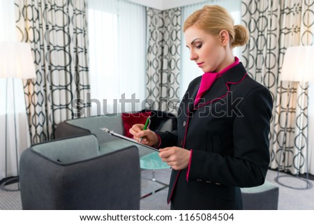 Housekeeping manager or assistant controlling hotel suit or suit with checklist on tidiness  #1165084504