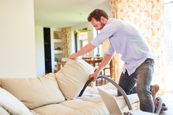 Houseman in the living room vacuuming on the couch during spring cleaning