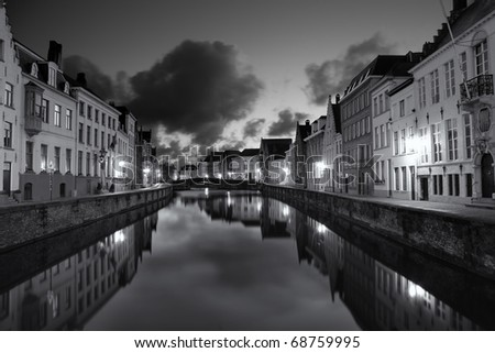 Houses along a canal at night in Bruges, Belgium, in a black and white composition