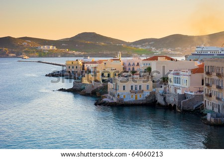 Houses along the sea on the island of Syros in Greece  at sunset. Classic architecture Greek islands.