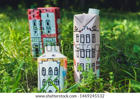 Houses and toy cars made from milk bags on grass. DIY paper milk bag. Creative paper milk bag ideas. Recycle crafts.