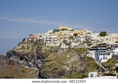 Houses, buildings, and cafes built into the side of the mountain in Santorini Greece