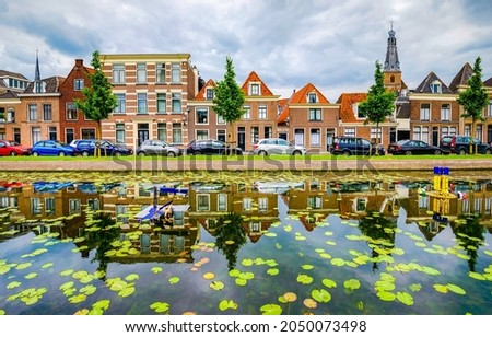 Houses by the blooming water of the city river canal. Canal in town. River canal water reflection in town
