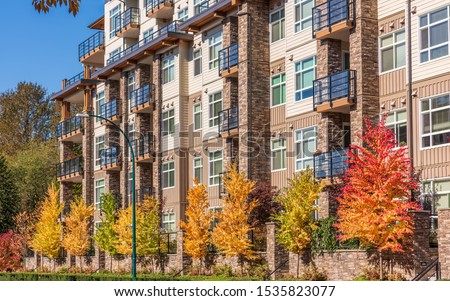 Houses in suburb with Fall Foliage in the north America. Luxury houses with nice yellow and red coloured landscape.