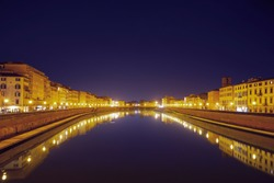 Houses lit with golden light and their reflections in the Arno River at night in Pisa, Italy. Panoramic view