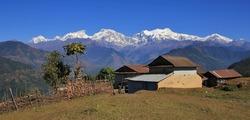 Houses near Ghale Gaun and snow capped Manaslu range. Rural scene in Nepal.