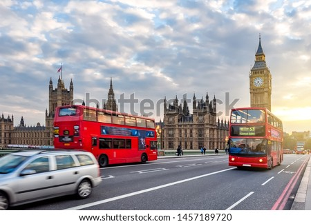 Houses of Parliament with Big Ben and double-decker buses on Westminster bridge at sunset, London, United Kingdom