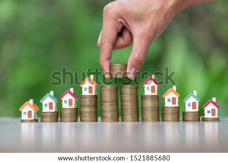 Houses on stairs, coins, houses Models on hand coins are about to put down coins, real estate concepts, mortgages and investments, save money or invest for future houses, areas to enter text.