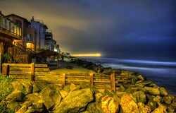 Houses on the coast in the late evening. Coastal houses in evening. Evening light at coasline. Coasline evening panorama