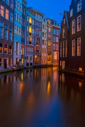 Houses over canal with reflections at night close up, Amstardam, Netherlands