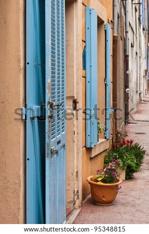 Houses with blue shutters in a row  in a small village in Provence in France.