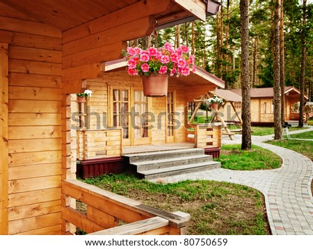 Houses with flowers in the pine forest - stock photo