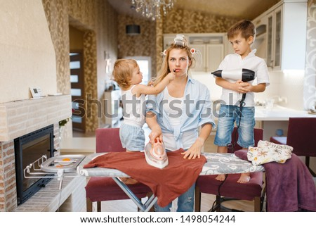 Housewife and kids playing with hair dryer