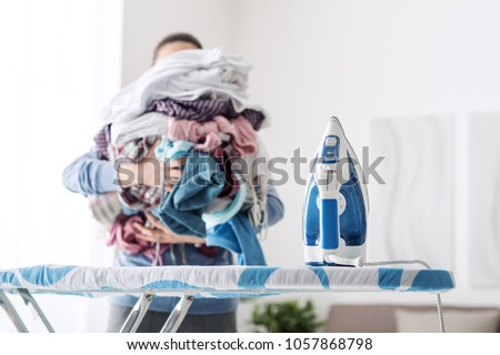 Housewife bringing a huge pile of laundry on the ironing board, boring household chores concept