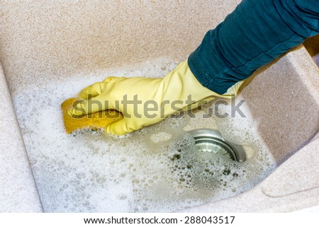 housewife clean the kitchen granite sink with a sponge