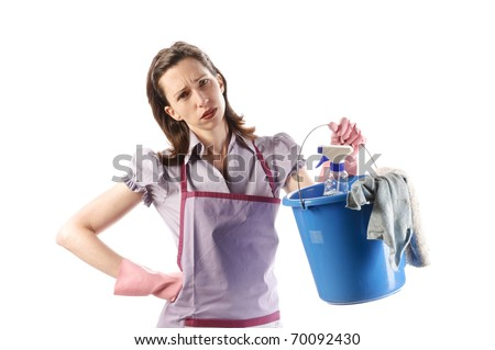 Housewife, cleaning lady with long dark blond hair and apron with the housework isolated on a white background. She holds a bucket of cleaning supplies into the camera.