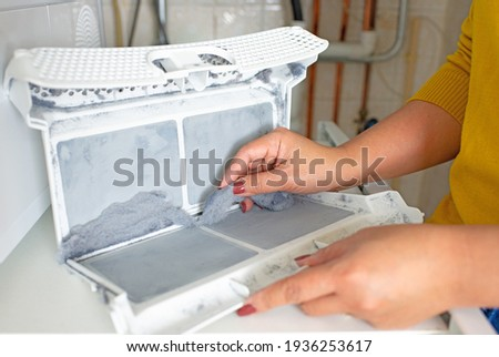 Housewife cleanup lints and dirt from tumble dryer filter. Clothes dryer lint filter that is covered with lint. Taking the lint out from dirty air filter of the dryer machine before use the machine. Stockfoto ©
