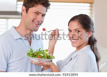 Housewife feeding her husband in their kitchen