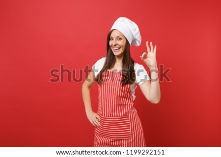 Housewife female chef cook or baker in striped apron, white t-shirt, toque chefs hat isolated on red wall background. Beautiful pensive housekeeper woman making okay sign. Mock up copy space concept