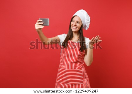 Housewife female chef cook or baker in striped apron, white t-shirt, toque chefs hat isolated on red wall background. Smiling fun woman doing selfie shot on mobile phone. Mock up copy space concept
