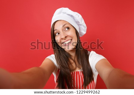 Housewife female chef cook or baker in striped apron, white t-shirt, toque chefs hat isolated on red wall background. Close up housekeeper woman doing taking selfie shot. Mock up copy space concept