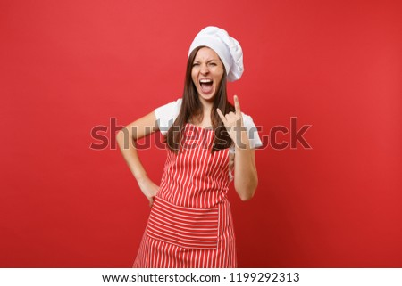 Housewife female chef cook or baker in striped apron white t-shirt toque chefs hat isolated on red wall background. Happy housekeeper woman depicting heavy metal rock sign. Mock up copy space concept #1199292313