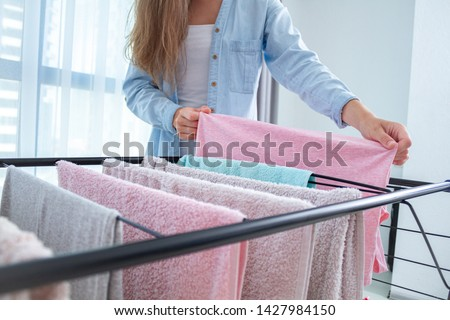 Housewife hangs washed clothes on the clothes dryer