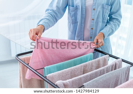 Housewife hangs wet laundry on the clothes dryer