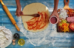 Housewife holding saucers with natural ketchup, which she spread on thin dough, spread out near all the ingredients for pizza