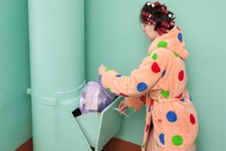 housewife in a orange dressing gown with polka dots and curlers on her head throws a bag of trash into the garbage chute