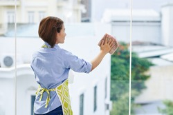 Housewife in apron cleaning big windows in her apartment