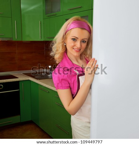 Housewife in the kitchen near the refrigerator