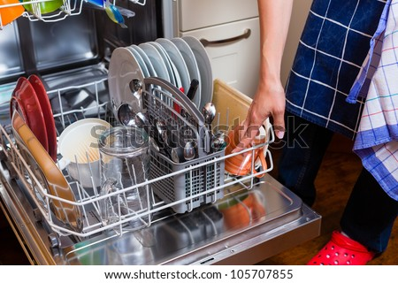 Housewife is doing the dishes with dishwasher, cropped image