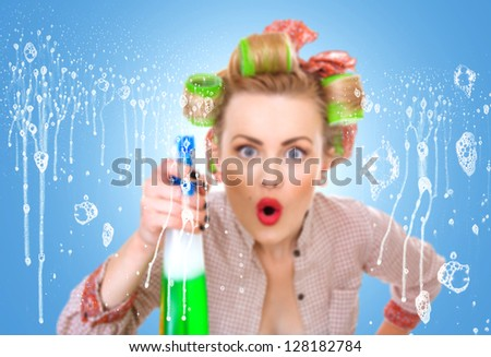 Housewife  or woman behind window spraying the cleaner on glass. Focus on soap