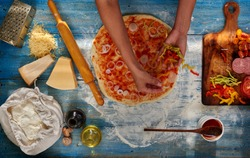 Housewife preparing a pizza for your family, arranges all the ingredients in the order, onions, tomatoes, peppers, sausage falls asleep all the cheese on top