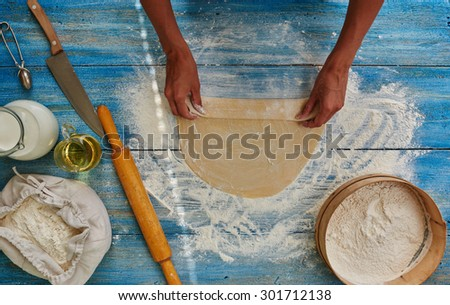 Housewife Roll out the dough and makes him roll which is baked in the oven