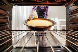 Housewife taking cheesecake out of oven in kitchen. View from inside of the oven. Woman wearing black apron and colorful oven mitt.