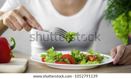 Housewife taking green lettuce salad from white plate in kitchen, fresh food #1052791139