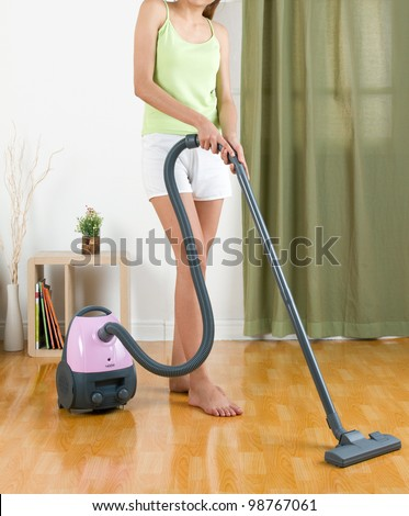 Housewife using vacuum cleaner machine to clean the floor
