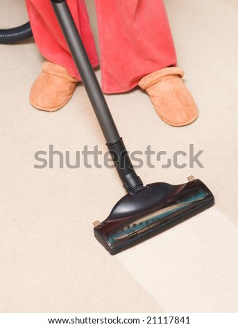 Housewife vacuum a carpet. Focus on tube.