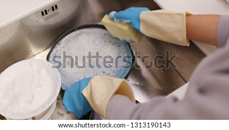 Housewife wash dishes in the kitchen