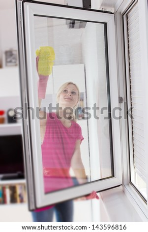 Housewife with protective glove washing the window glass.