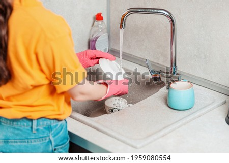 Housework. A woman in pink rubber gloves is washing a plate. Side view. Copy space. Stock photo ©