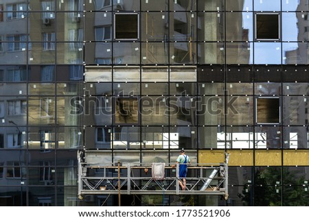 Housing development concept. Facade of new building under construction with glass windows and worker in scaffolding equipment