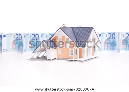Housing finance, building savings and realty financing (investments) concept. Money wall and model of the family house.