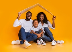 Housing For Young Family Concept. Young Black Father, Mother And Daughter Sitting Under Symbolic Roof Dreaming Of New Home Over Yellow Background
