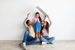 Housing for young family concept. Young eastern father, mother and daughter under symbolic roof dreaming of new home, sitting on floor over light wall