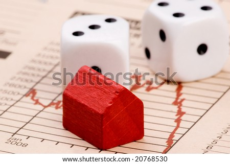 Housing market concept image with graph and toy house with dice